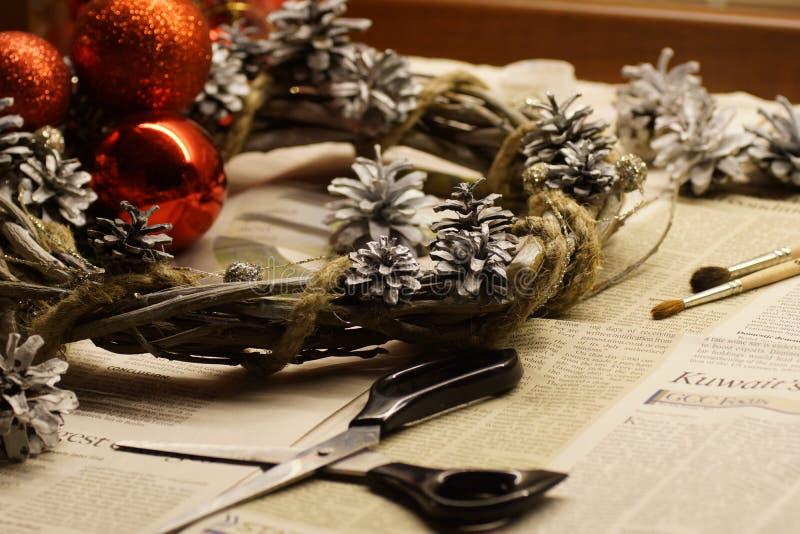 O processo de fazer uma grinalda do Natal com suas próprias mãos A grinalda do advento, ou a coroa do advento, são uma tradição c fotografia de stock royalty free