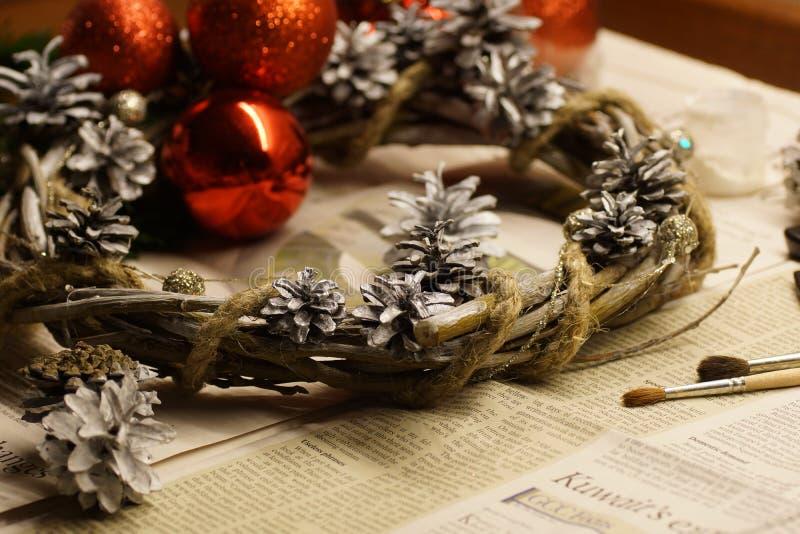 O processo de fazer uma grinalda do Natal com suas próprias mãos A grinalda do advento, ou a coroa do advento, são uma tradição c foto de stock