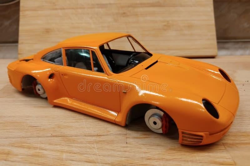 O processo de montar e de pintar o modelo ? escala do carro Carro de esportes alaranjado na miniatura imagem de stock
