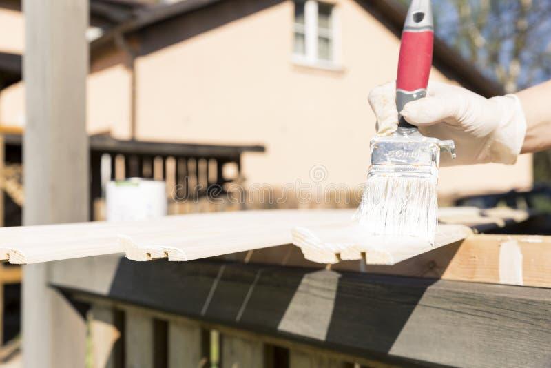 O processo de pintar um lath de madeira fora Conceito home da renovação fotografia de stock