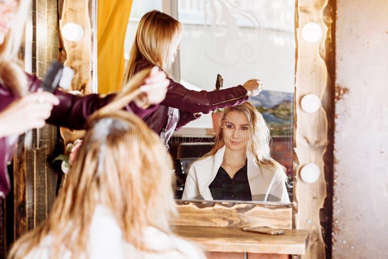 O processo de tratamento do cabelo, coloração de cabelo O cabeleireiro é cabelo fêmea de morte Cliente atrativo bonito que senta- fotos de stock