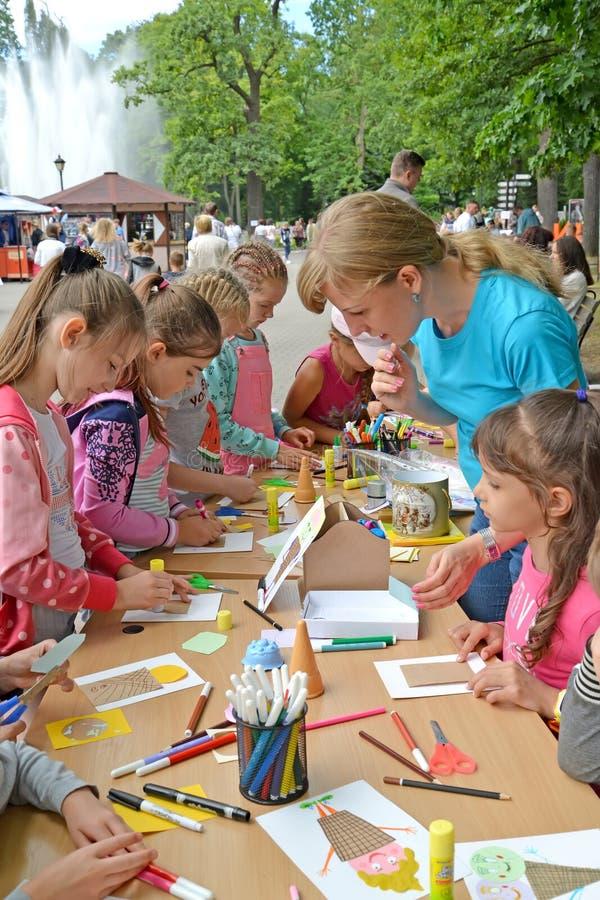 O professor é contratado com as crianças no applique do papel em uma classe mestra no parque fotos de stock royalty free