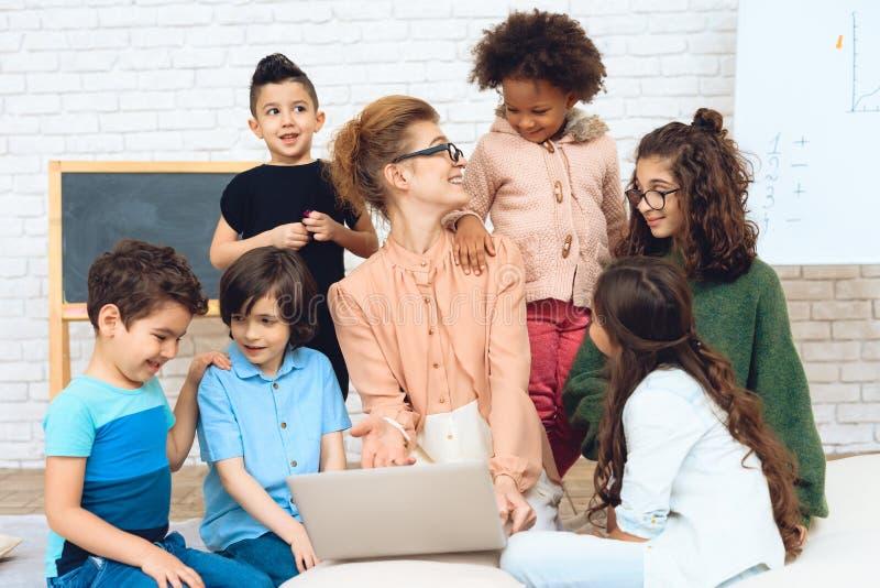 O professor agradável senta-se com alunos que a cercaram e estão olhando o portátil foto de stock