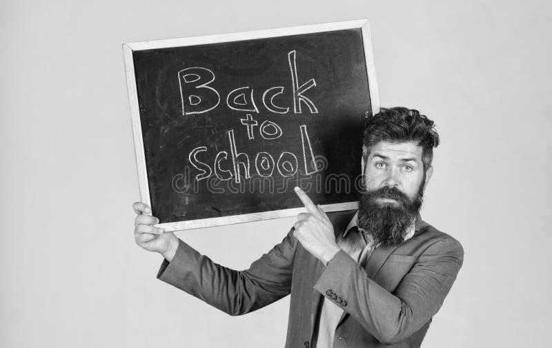 O professor anuncia de volta ao estudo, come?a ano escolar O homem farpado do professor est? e guarda o quadro-negro com inscri?? foto de stock royalty free
