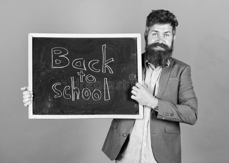 O professor anuncia de volta ?s fontes de escola novas da compra da escola O homem farpado do professor est? e guarda o quadro-ne fotos de stock royalty free