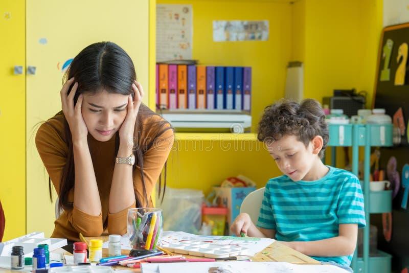 O professor asiático da mulher obtém a dor de cabeça com as crianças do menino impertinente no classr foto de stock royalty free