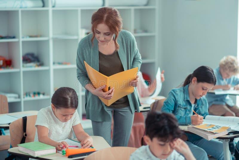 O professor atento que olha próximo em seus alunos trabalha imagem de stock