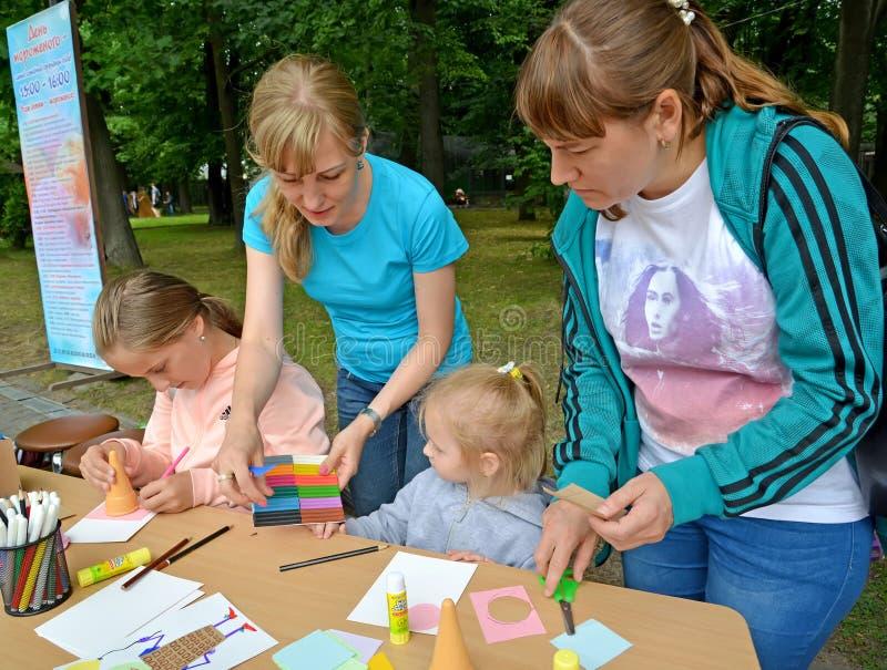 O professor dá ao plasticine da criança para a ocupação Classe do mestre do ` s das crianças no ar livre imagem de stock