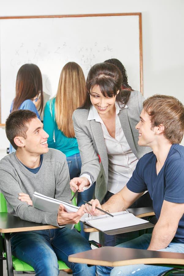 O professor dá lições privadas aos estudantes adolescentes foto de stock