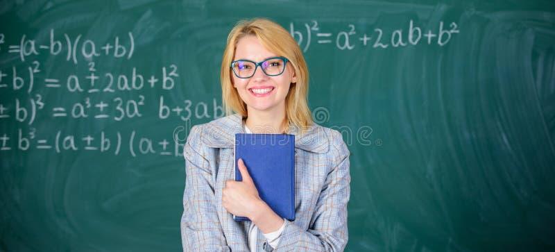 O professor da mulher com o livro na frente do quadro pensa sobre o trabalho Processo da cognição na aprendizagem Processo da cog imagem de stock