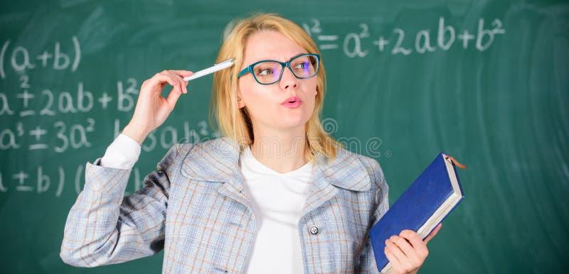 O professor da mulher com o livro na frente do quadro pensa sobre o trabalho Processo da cognição de adquirir o conhecimento comp imagens de stock royalty free