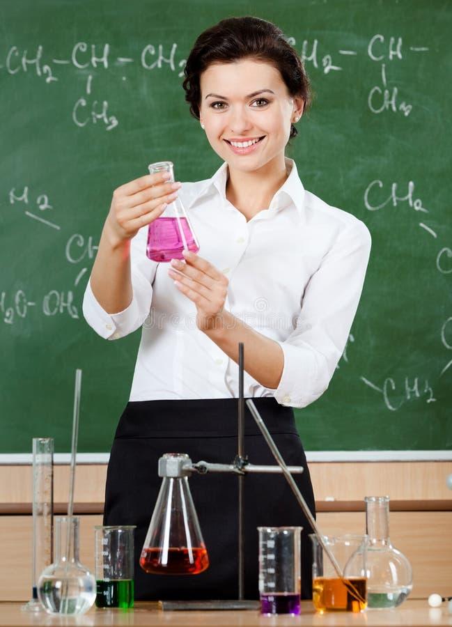 O professor da química do smiley entrega uma garrafa de Erlenmeyer imagem de stock royalty free