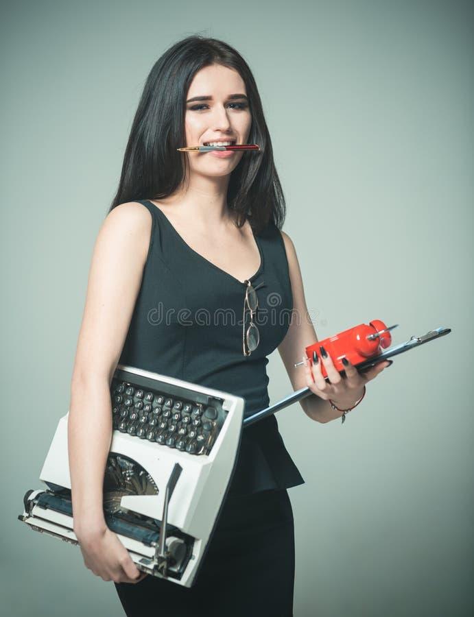 O professor da senhora leva o despertador e a programação da máquina de escrever Conceito a multitarefas Multitarefa bem sucedida imagens de stock