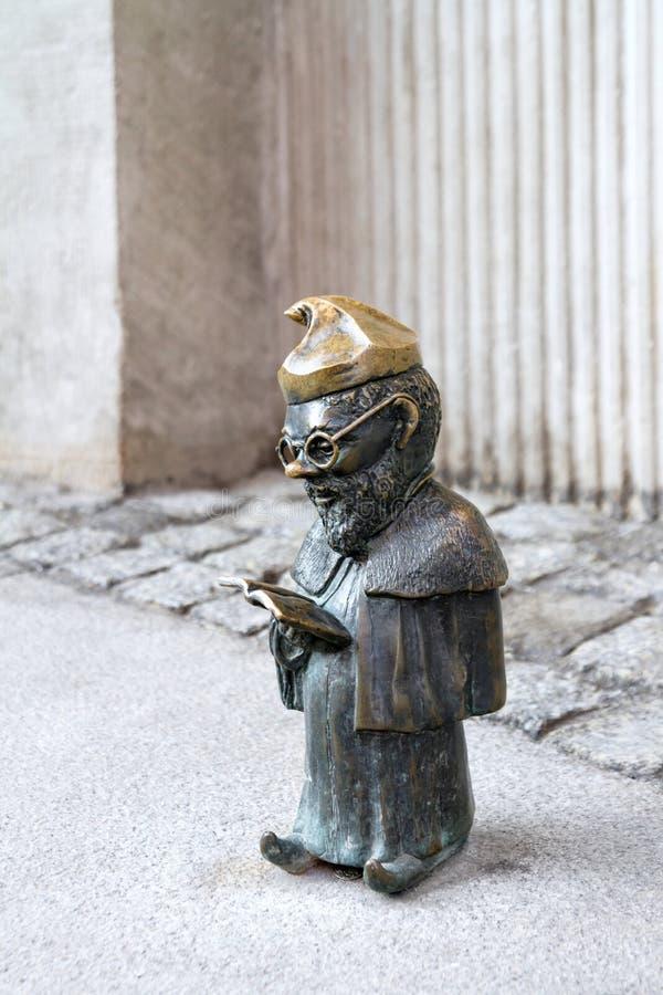 O professor de bronze pequeno do gnomo da estátua por nome -, gnomo na roupa professoral e com livro fotografia de stock royalty free