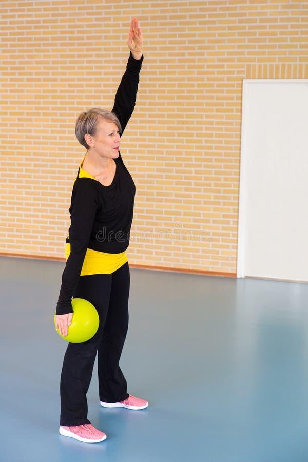 O professor de Gym com bola estica os músculos do braço na classe do gym imagens de stock royalty free