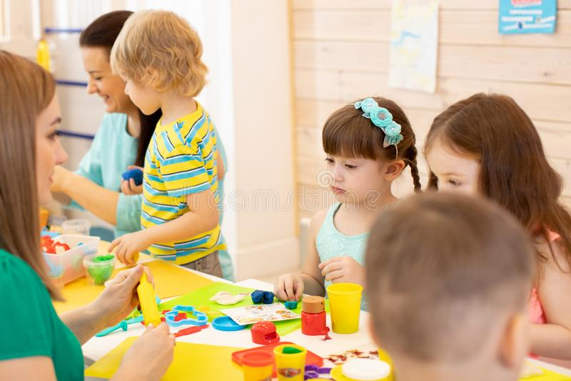 O professor de jardim de infância ensina o grupo de argila de modelagem das crianças fotografia de stock