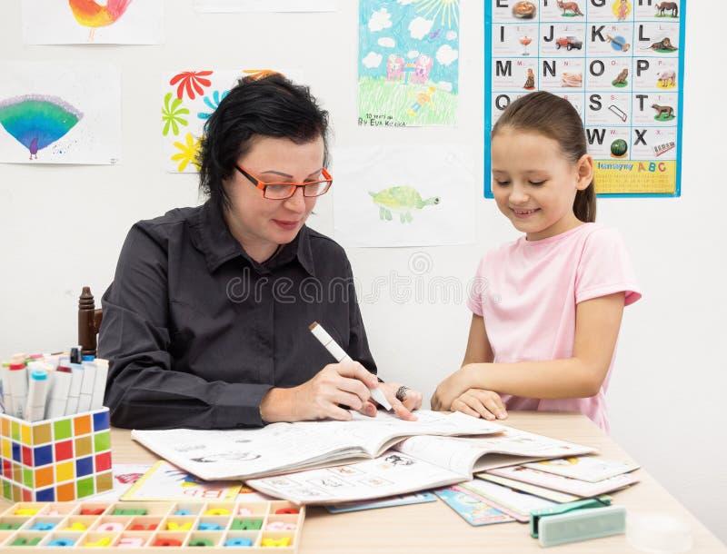 O professor de língua inglesa com criança verifica o caderno imagens de stock royalty free