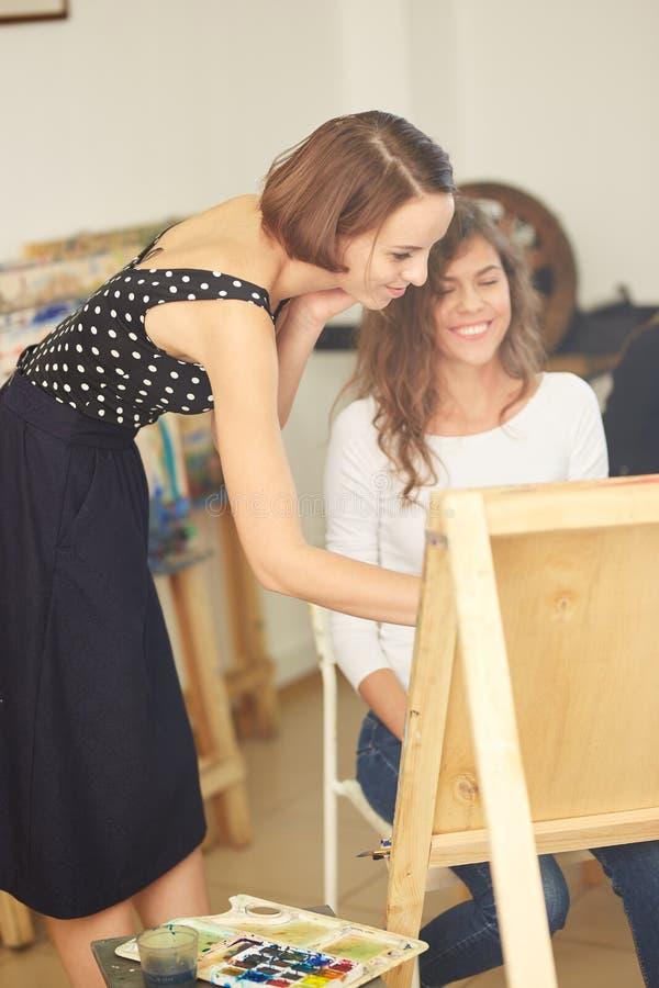 O professor de tiragem bonito ajuda a menina bonita nova com cabelo encaracolado marrom a pintar uma imagem na armação no fotos de stock royalty free