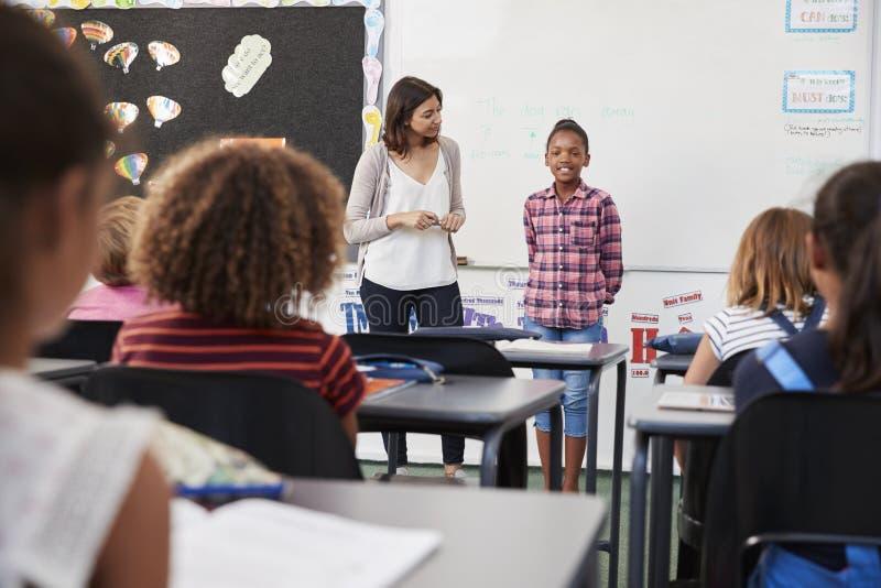 O professor e o aluno estão na parte dianteira da turma escolar elementar imagens de stock