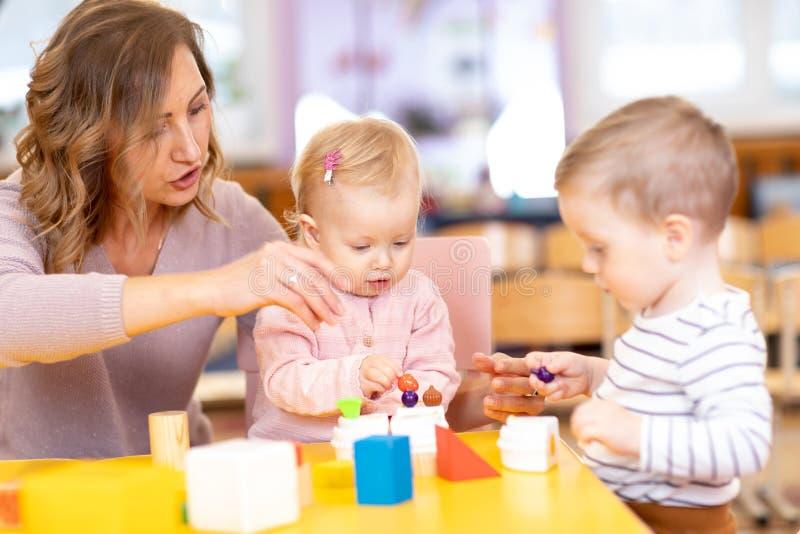 O professor e as crianças aprendem a cor e o tamanho ao jogar junto Conceito adiantado da educação fotos de stock