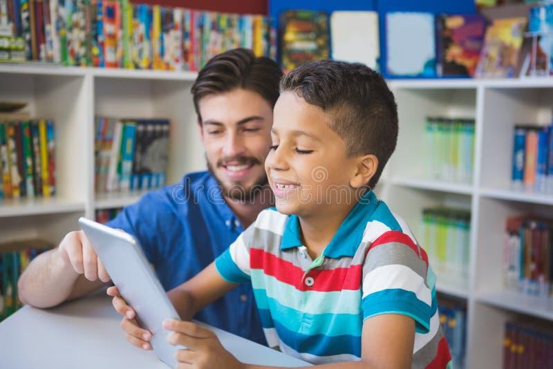O professor e a escola caçoam usando a tabela digital na biblioteca fotografia de stock royalty free