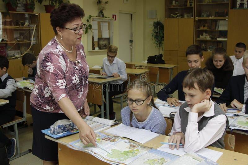 O professor ensina crianças da escola primária fotos de stock