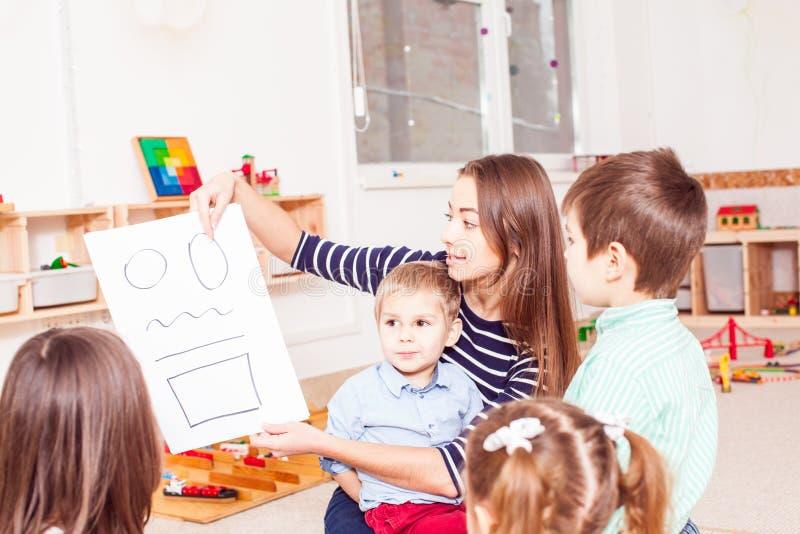 O professor ensina a crianças figuras diferentes imagens de stock royalty free