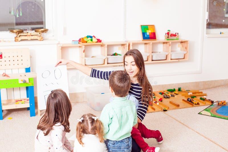 O professor ensina a crianças figuras diferentes foto de stock royalty free