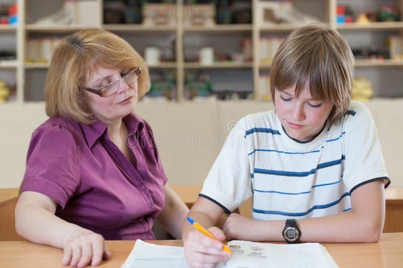 O professor ensina um aluno em uma tabela na sala de aula fotografia de stock