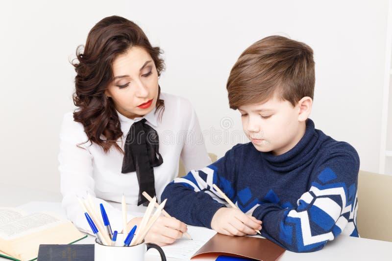 O professor fêmea ajuda o menino adolescente a fazer seus trabalhos de casa Fazendo trabalhos de casa junto foto de stock royalty free
