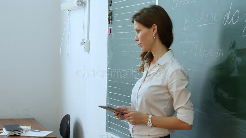 O professor fêmea consideravelmente novo diz algo com a tabuleta em suas mãos fotos de stock royalty free