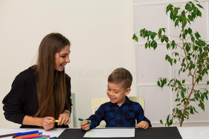 O professor fêmea ensina um rapaz pequeno tirar na tabela imagem de stock royalty free
