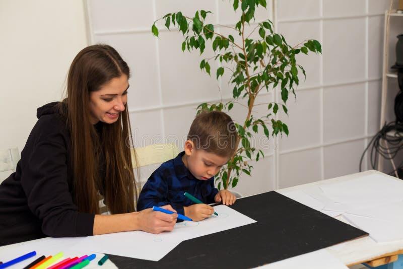 O professor fêmea ensina um rapaz pequeno tirar na tabela fotografia de stock