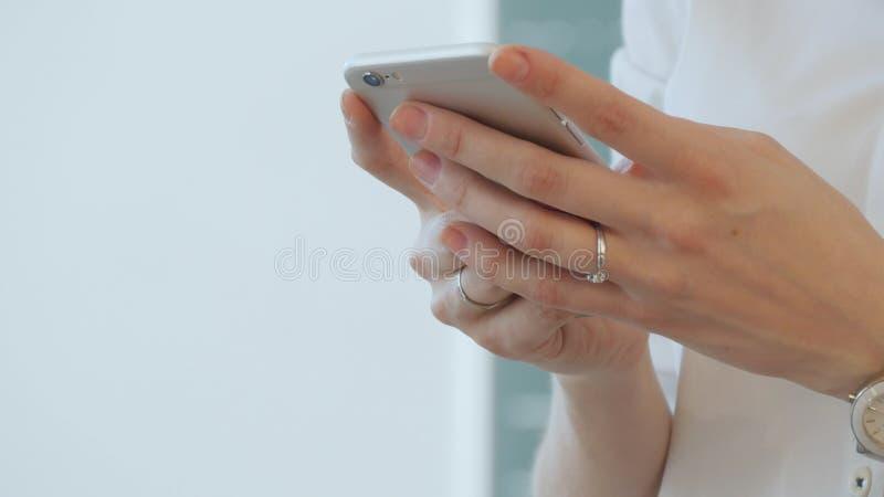 O professor fêmea novo escreve SMS a seu telefone celular foto de stock