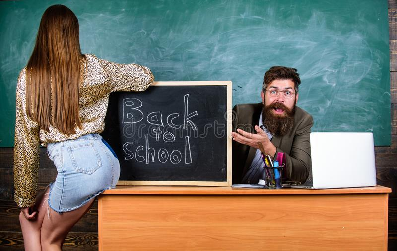 O professor indignante senta o fundo do quadro da tabela Regras da disciplina e do comportamento da escola Estudante na mini saia imagem de stock