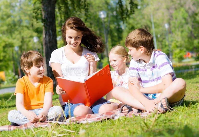 O professor lê um livro às crianças em um parque do verão fotos de stock