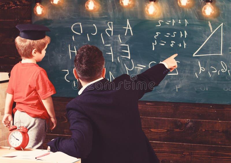 O professor masculino novo guia seu estudante da crian?a ? aprendizagem ao apontar e ao olhar o quadro com garranchos sobre imagens de stock royalty free