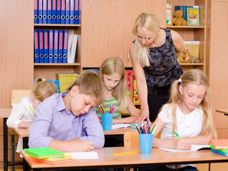O professor novo ajuda estudantes da escola primária no exame fotos de stock royalty free