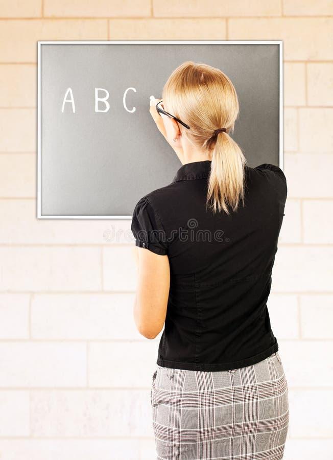 O professor novo escreve no quadro-negro fotos de stock royalty free