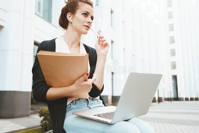 O professor novo prepara-se para a leitura e procura-se para obter informações sobre do Internet com um laptop que senta-se na ru fotos de stock royalty free