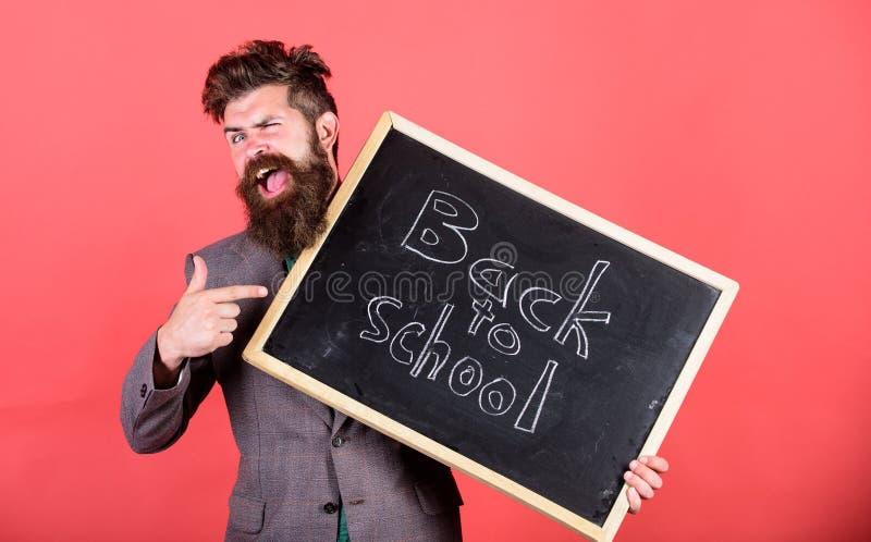 O professor ou o professor derem boas-vindas a estudantes quando quadro das posses com inscrição de volta à escola Continue a edu imagens de stock royalty free