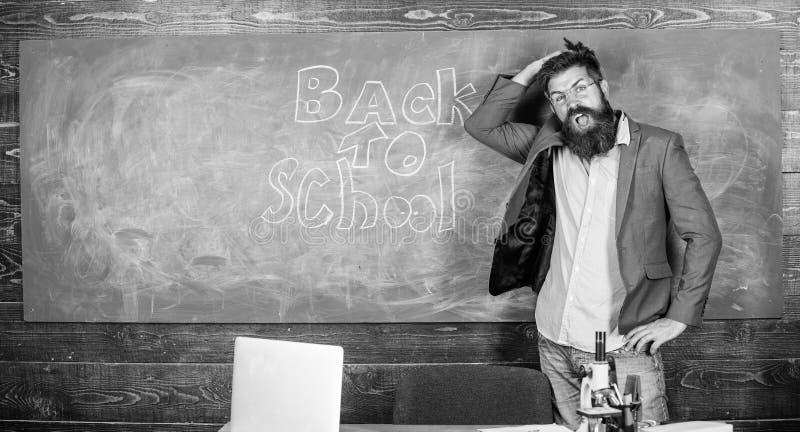 O professor ou o professor derem boas-vindas a estudantes quando suportes perto do quadro com inscrição de volta à escola Convide imagem de stock