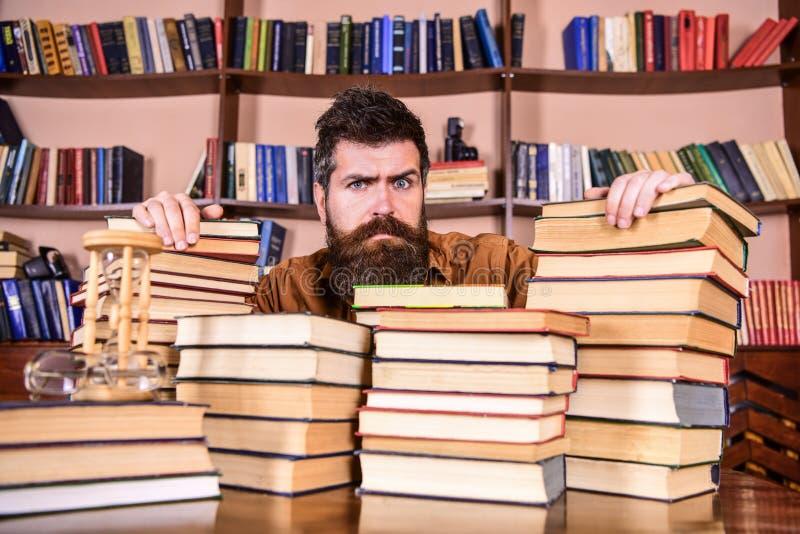 O professor ou o estudante com barba sentam-se na tabela com os livros, defocused Homem na cara séria entre pilhas dos livros, qu fotografia de stock royalty free
