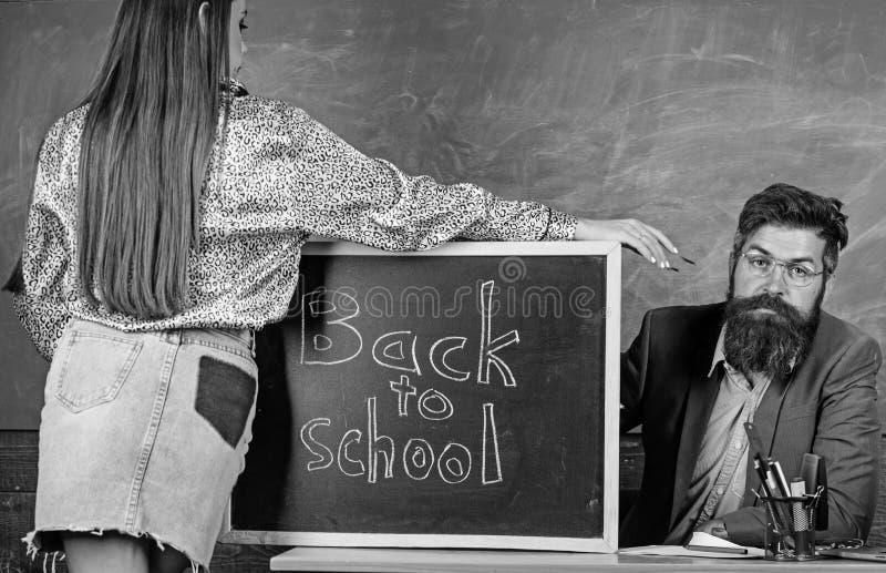 O professor restrito senta o fundo do quadro da tabela O estudante na mini saia com nádegas agradáveis está o quadro-negro próxim imagem de stock royalty free