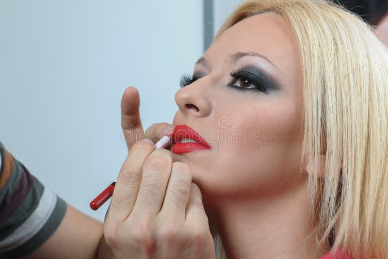 O profissional compõe o artista que aplica o batom a uma cara modelo nova imagem de stock royalty free