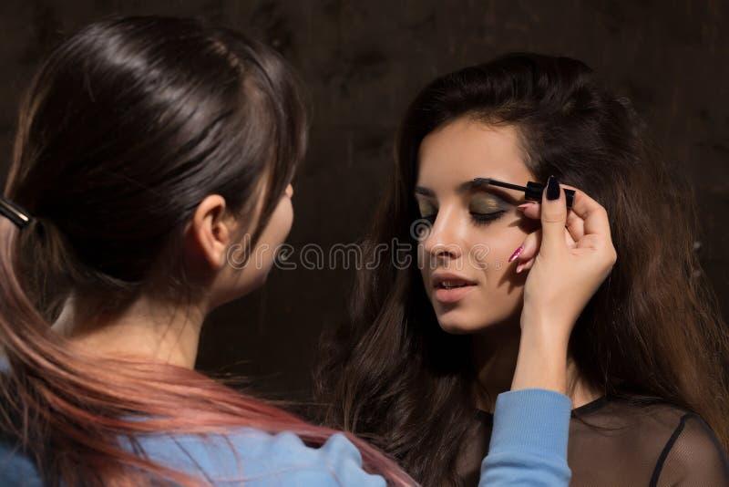 O profissional compõe o artista que prepara o modelo antes da sessão de foto fotos de stock