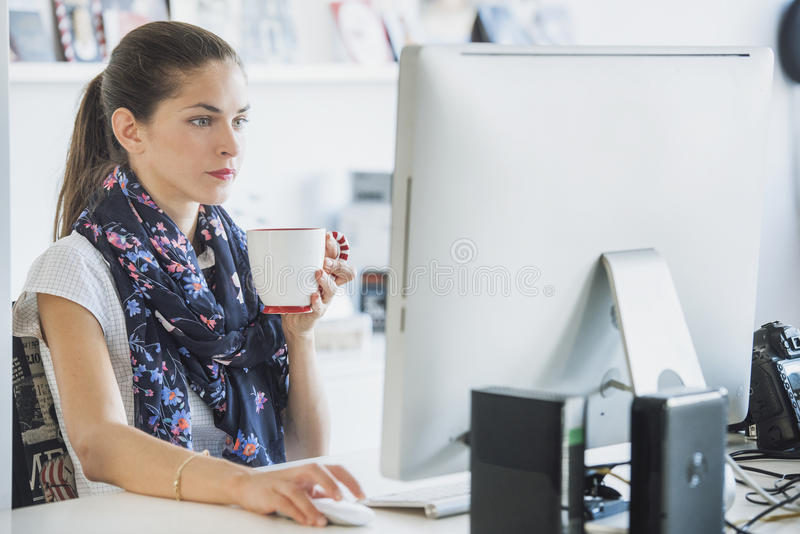 O profissional da mulher está usando um computador que bebe uma bebida fotografia de stock royalty free