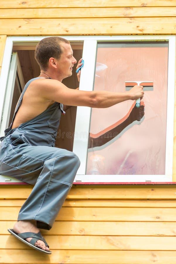 O profissional masculino nos macacões limpa a janela imagem de stock