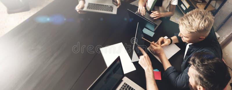 O profissional novo dá algumas ideias novas sobre o projeto a seus sócios na sala de reunião Executivos que discutem sobre fotos de stock royalty free