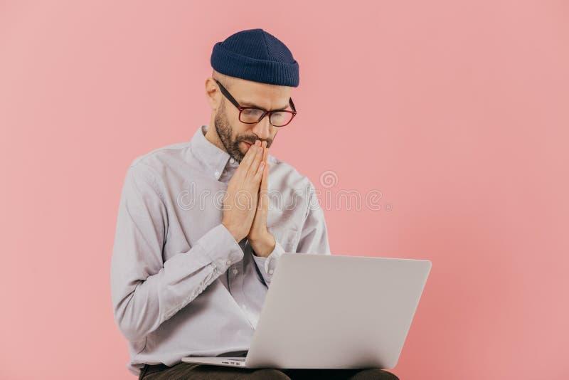 O programador masculino profissional mantém Hans em rezar o gesto, olha a tela do laptop, acredita no resultado bem sucedido de fotografia de stock royalty free